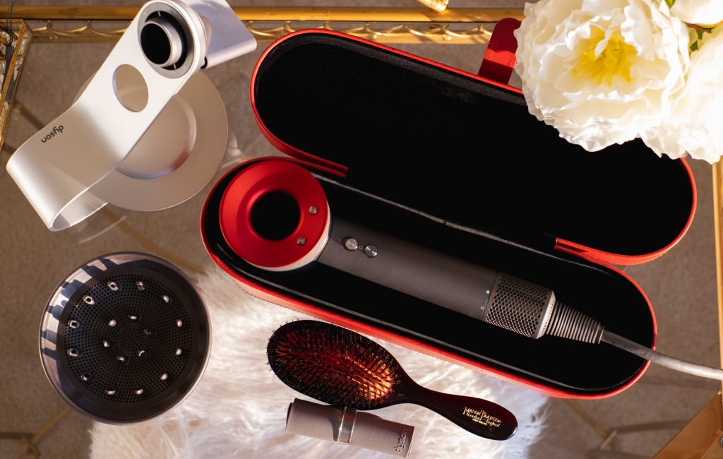 Red/Iron Dyson Supersonic Hair Dryer in Red Case on vanity table
