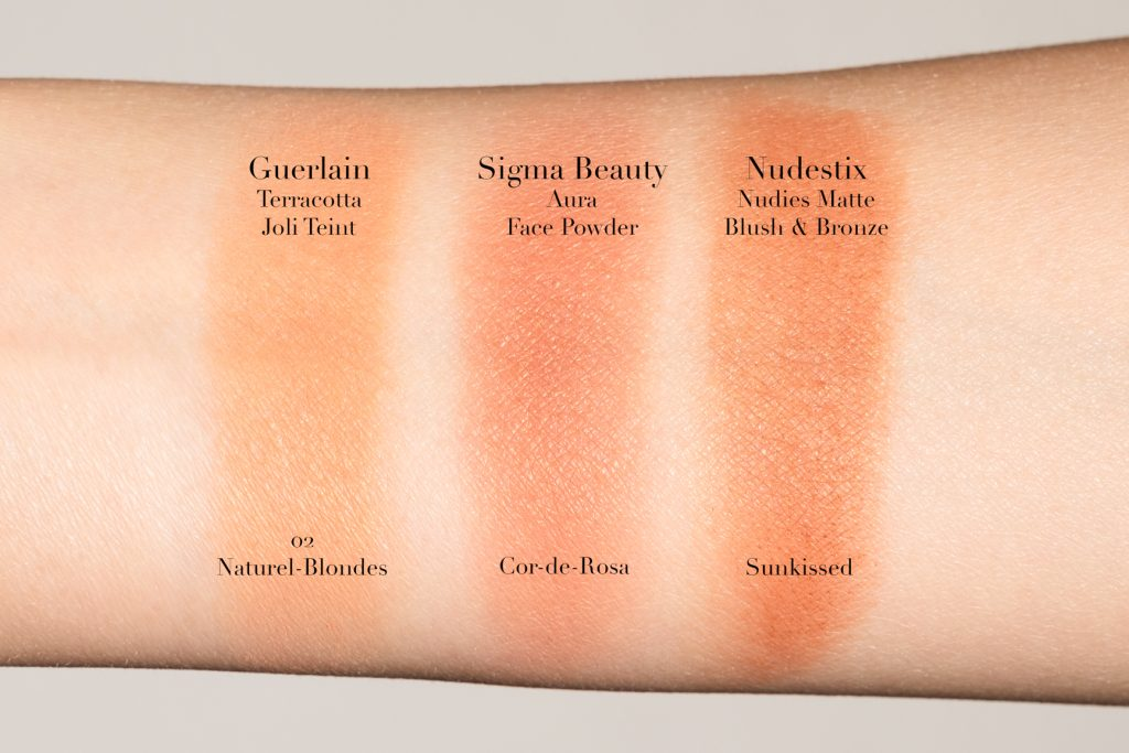 comparing swatches of Guerlain Terracotta Joli Teint Natural Healthy Glow Ppwder Duo in 02 Naturel/Blondes, Sigma Beauty Aura Powder - Face Powder in Cor-de-Rosa, Nudestix Nudies Matte Matte Blush & Bronze - All Over Bronze Color in Sunkissed