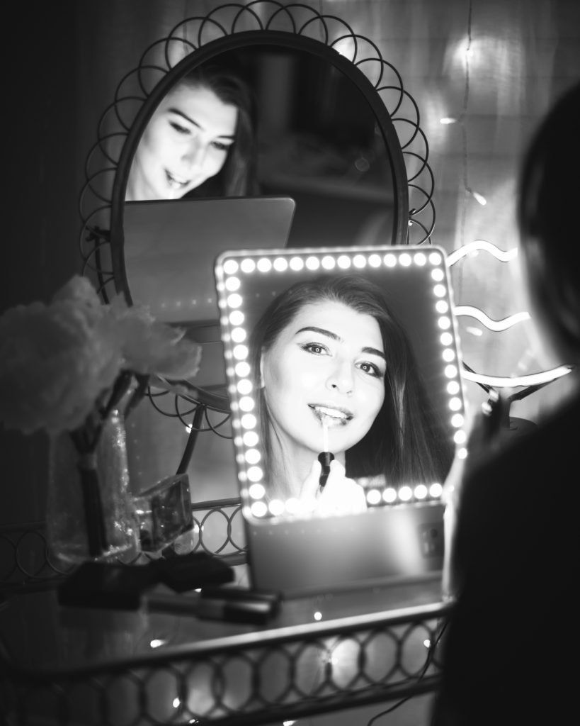 RIKI LOVES RIKI Skinny Vanity Lighted Mirror on vanity table with Farah Gasimzade, Founder of Sun Kissed Blush, in reflection